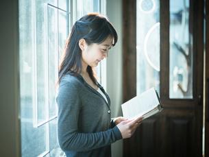 窓辺で本を読む女性の横顔の写真素材 [FYI02617072]