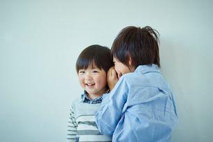 内緒話をする兄弟の写真素材 [FYI02617077]