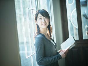 本を持ち窓の外を見る女性の写真素材 [FYI02617112]