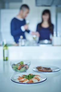 テーブルの上の料理とキッチンのミドル夫婦の写真素材 [FYI02617116]