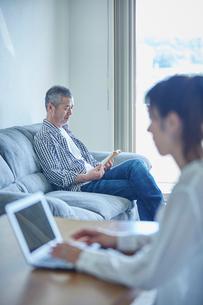 ノートパソコンを操作する女性と読書をする男性の写真素材 [FYI02617150]