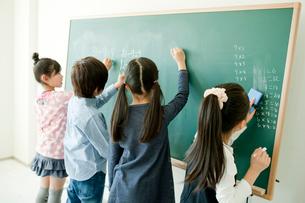 黒板で算数の問題を解く小学生4人の写真素材 [FYI02617153]
