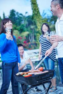 ガーデンパーティーでバーベキューをする2組の夫婦の写真素材 [FYI02617181]