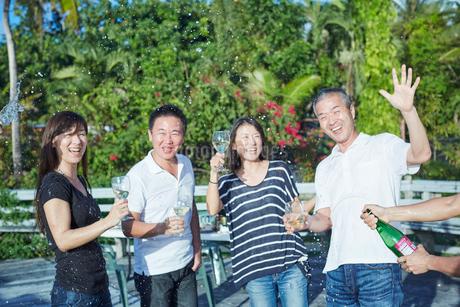 シャンパンシャワーを楽しむ2組の夫婦の写真素材 [FYI02617211]