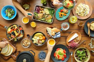 洋食がのった食卓と食事をする4人の手元の写真素材 [FYI02617259]
