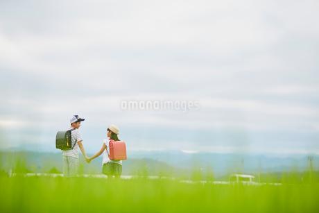 手をつなぐ小学生の兄妹と空の写真素材 [FYI02617263]