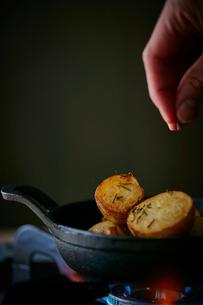 ジャガイモにローズマリーをかける女性の手元の写真素材 [FYI02617288]