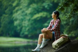 岩の上に座る女性とリュックサックの写真素材 [FYI02617297]