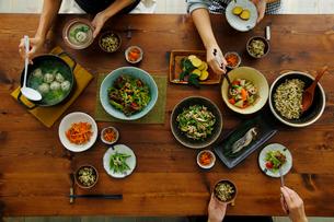 和食がのった食卓と食事をする3人の手元の写真素材 [FYI02617980]