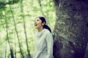 木にもたれて音楽を聴く女性の写真素材 [FYI02618092]