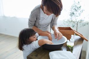 洗面器に手を入れる女の子と母親の写真素材 [FYI02620015]