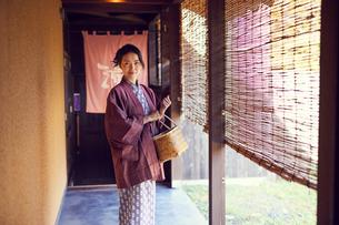 温泉の入り口に立つ浴衣姿のミドル女性の写真素材 [FYI02620250]
