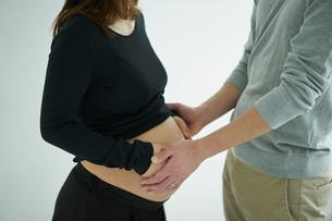 お腹に触れる妊婦と夫の写真素材 [FYI02620290]