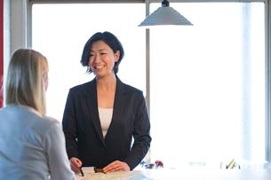 外国人女性と話す旅行代理店の日本人スタッフの写真素材 [FYI02620319]