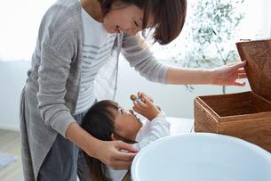 小物入れから物を取り出す女の子と母親の写真素材 [FYI02620347]