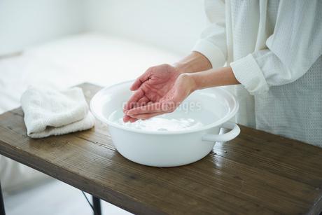 ウォッシュタブの水をすくう女性の手元の写真素材 [FYI02620366]