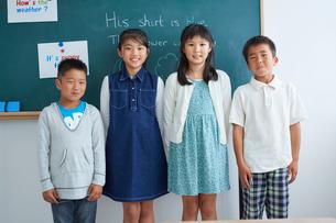黒板の前に立つ小学生4人の写真素材 [FYI02620392]