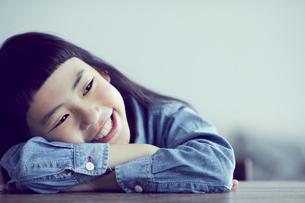 机に伏せる笑顔の女の子の写真素材 [FYI02620441]