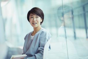 本を持ち窓の外を眺める女性の写真素材 [FYI02620442]