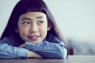 机に伏せる笑顔の女の子の写真素材 [FYI02620475]