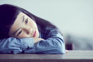 机に伏せる女の子の写真素材 [FYI02620576]