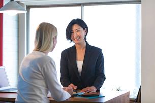 外国人女性と話す旅行代理店の日本人スタッフの写真素材 [FYI02620678]