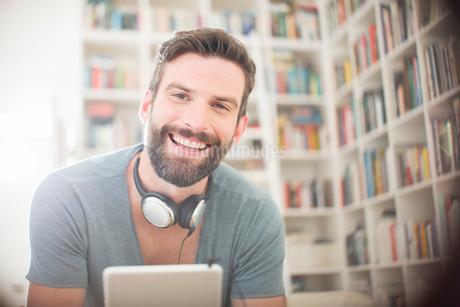 Smiling man using digital tablet in living roomの写真素材 [FYI02628750]