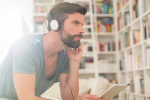 Man listening to music in living roomの写真素材 [FYI02628880]