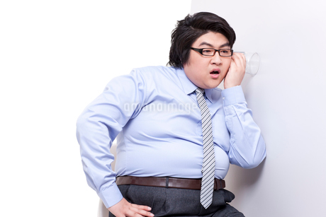 Overweight businessman doing eavesdroppingの写真素材 [FYI02630038]