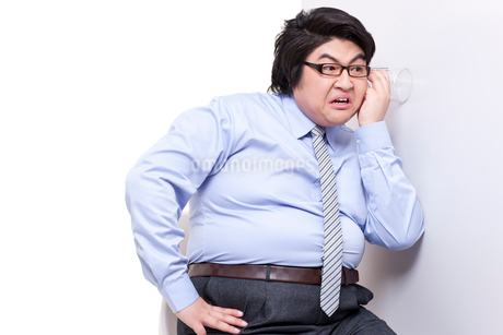 Overweight businessman doing eavesdroppingの写真素材 [FYI02630138]