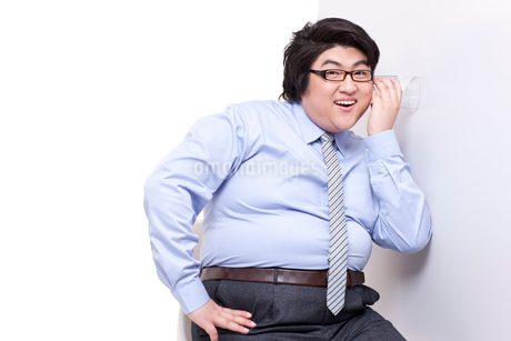 Overweight businessman doing eavesdroppingの写真素材 [FYI02630223]