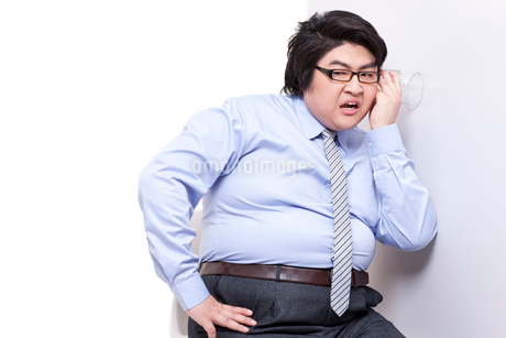 Overweight businessman doing eavesdroppingの写真素材 [FYI02630390]