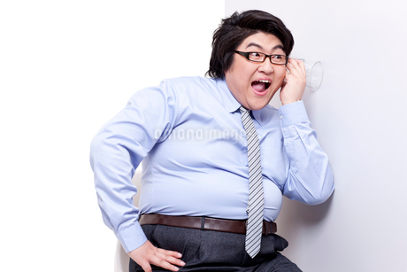 Overweight businessman doing eavesdroppingの写真素材 [FYI02630410]