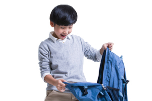 Cute schoolboy opening book bag with surpriseの写真素材 [FYI02631611]