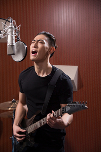 Young man singing with guitar in recording studioの写真素材 [FYI02634455]