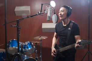 Young man singing with guitar in recording studioの写真素材 [FYI02634657]
