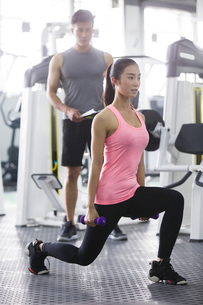 Young woman working with trainer at gymの写真素材 [FYI02634727]