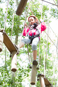 Little girl playing in tree top adventure parkの写真素材 [FYI02634810]