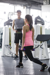 Young woman working with trainer at gymの写真素材 [FYI02634904]
