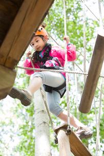 Little girl playing in tree top adventure parkの写真素材 [FYI02634908]