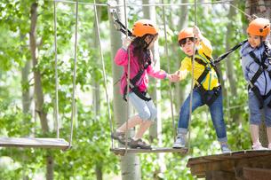 Happy children playing in tree top adventure parkの写真素材 [FYI02634981]
