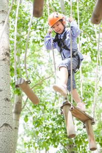 Little girl playing in tree top adventure parkの写真素材 [FYI02635060]