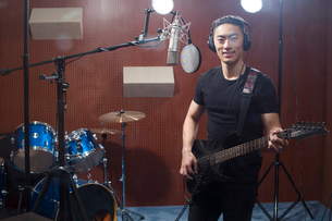 Young man singing with guitar in recording studioの写真素材 [FYI02635121]