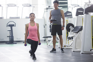 Young woman working with trainer at gymの写真素材 [FYI02635258]