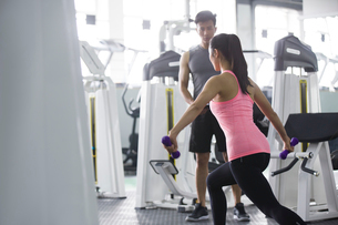 Young woman working with trainer at gymの写真素材 [FYI02635302]