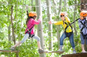 Happy children playing in tree top adventure parkの写真素材 [FYI02635407]