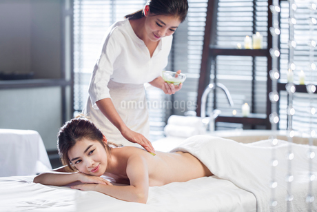 Young woman receiving back massage at spa centerの写真素材 [FYI02637039]