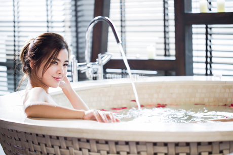 Beautiful young woman in bathtub with rose petalsの写真素材 [FYI02637084]