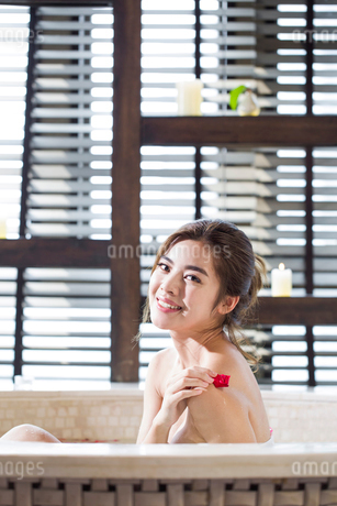 Beautiful young woman in bathtub with rose petalsの写真素材 [FYI02637089]