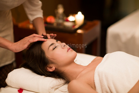 Young woman receiving facial massage at spa centerの写真素材 [FYI02637103]